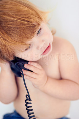 Buy stock photo Shot of a little girl talking on a landline phone