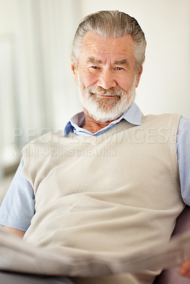 Buy stock photo Portrait of a senior man  smiling at the camera while reading the newspaper