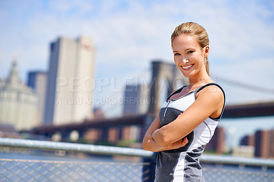 Buy stock photo Portrait of an attractive young woman in sports clothing standing against a city background