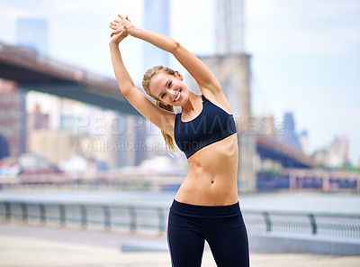 Buy stock photo Portrait of a beautiful woman stretching before her run in the city
