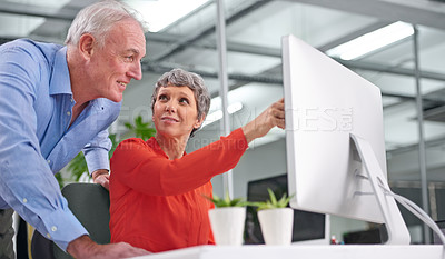 Buy stock photo Shot of two mature business colleagues discussing work at a desktop computer