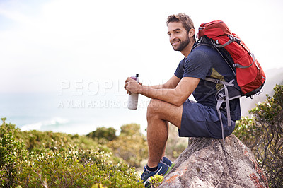 Buy stock photo Shot of a handsome man taking a break from his hike on a sunny day