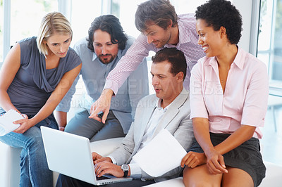 Buy stock photo Young business man pointing on laptop screen with his team in the office