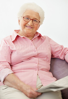 Buy stock photo Portrait of a relaxed senior woman sitting on the sofa and reading the newspaper