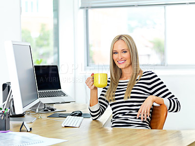 Buy stock photo Shot of a beautiful young woman working at her office desk while enjoying a drink