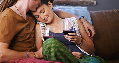Buy stock photo Shot of a young dreadlocked couple drinking wine on their sofa