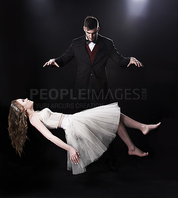 Buy stock photo Shot of vaudeville magician levitating a woman on stage