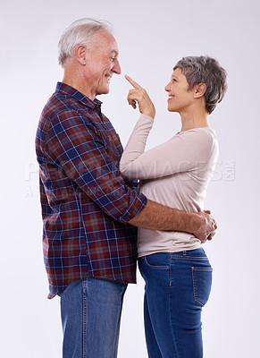 Buy stock photo Studio shot of an affectionate elderly couple against a gray background