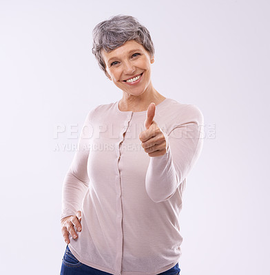 Buy stock photo Studio portrait of an mature woman giving thumbs up against a white background