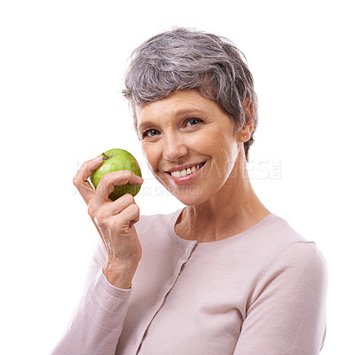 Buy stock photo Studio portrait of a happy mature woman holding an apple isolated on white