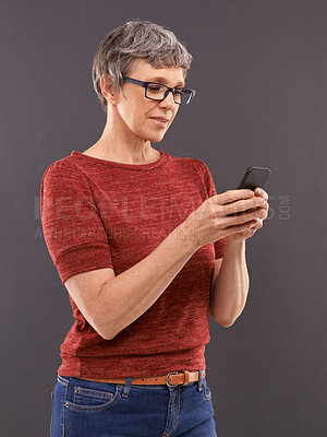 Buy stock photo Studio shot of an elderly woman using a mobile phone against a gray background