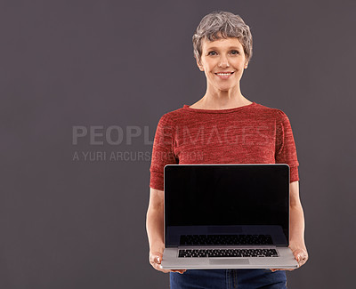 Buy stock photo Studio portrait of an elderly woman holding a laptop against a gray background