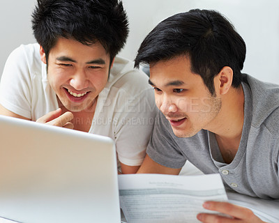 Buy stock photo Shot of a young gay couple relaxing with their laptop in bed