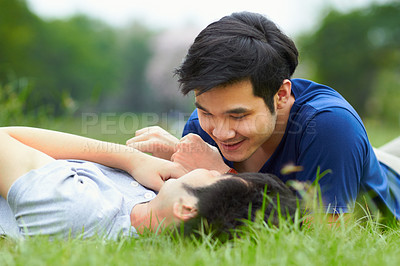 Buy stock photo Shot of an affectionate young gay couple lying on the grass together