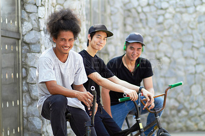 Buy stock photo A group of young bmx riders relaxing together