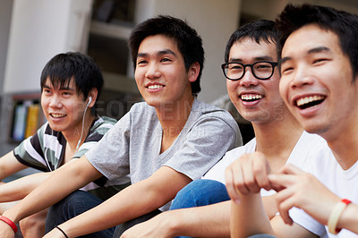Buy stock photo Shot of a group of asian friends sitting outdoors