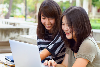 Buy stock photo Shot of two female students using a laptop together on campus