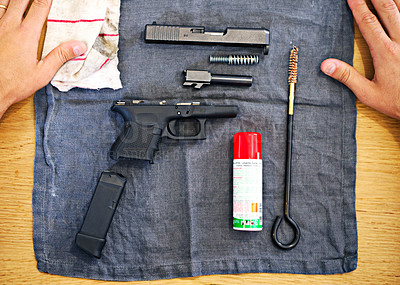 Buy stock photo A shot of a disassembled gun lying on a table top