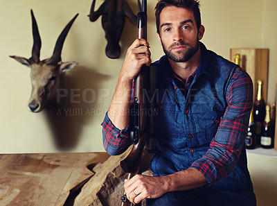 Buy stock photo Portrait of a hunter sitting in front of his trophies