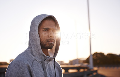 Buy stock photo A focused young sportsman wearing a hoodie and looking away