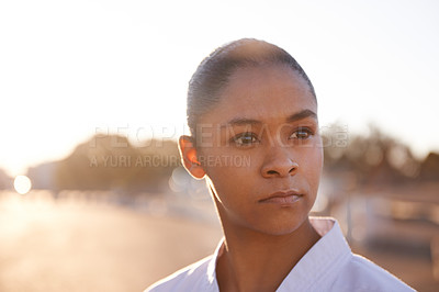 Buy stock photo A focused young sportswoman wearing a gi and looking away