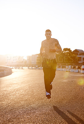 Buy stock photo A young fighter jogging while outdoors