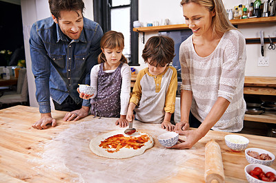 Buy stock photo A family making pizza together at home