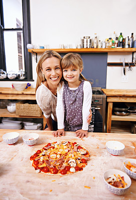 Buy stock photo A happy mother and daughter in the kitchen at home with a homemade pizza before them