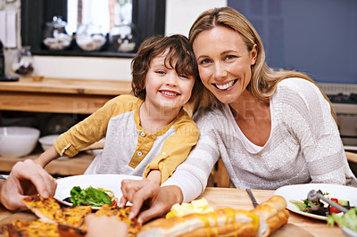 Buy stock photo A little boy and his mom eating dinner at the table