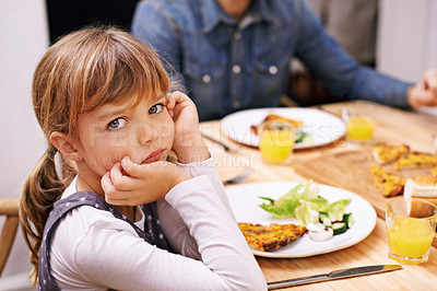 Buy stock photo A little girl sitting at the dinner table with a sulky look