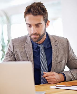 Buy stock photo Shot of a handsome businessman using a laptop