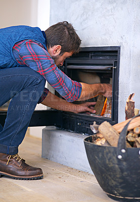 Buy stock photo Shot of a young man building a fire in his fireplace at home