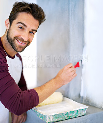 Buy stock photo Shot of a young man painting a wall indoors