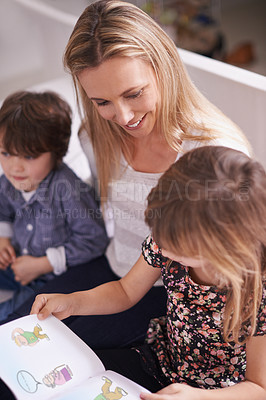 Buy stock photo Shot of a mother reading with her children at home