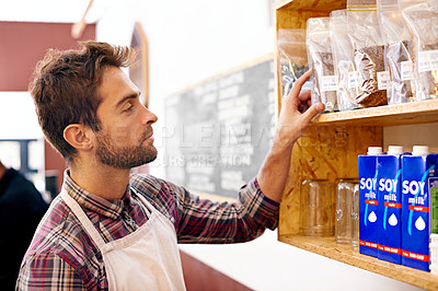Buy stock photo Shot of a barista counting his merchandise