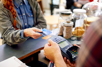 Buy stock photo Shot of a customer paying for their order with a credit card machine in a cafe