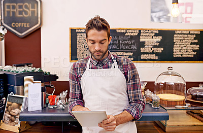 Buy stock photo Shot of a young barista using a digital tablet in a cafe