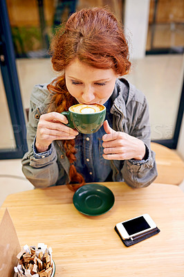 Buy stock photo A young woman drinking a cappuccino in a coffee shop