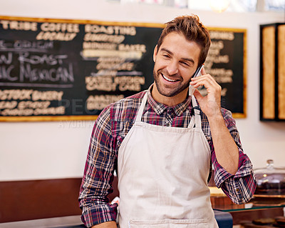 Buy stock photo Shot of a barista talking on a cellphone in a cafe