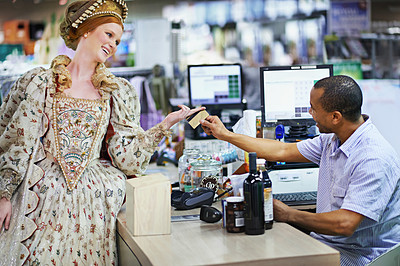 Buy stock photo Shot of a queen buying goods at a supermarket and paying with a credit card