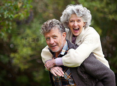 Buy stock photo Shot of a loving senior couple being playful outside