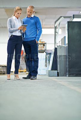 Buy stock photo Two professional factory managers using a tablet to monitor productivity