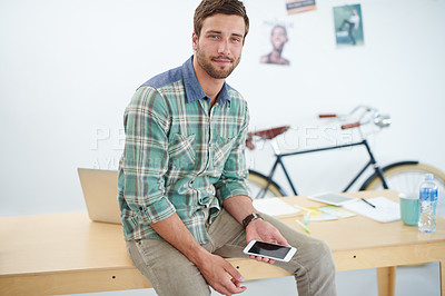Buy stock photo Portrait of a casually-dressed young man using a digital tablet at his desk. The commercial designs displayed in this image represent a simulation of a real product and have been changed or altered enough by our team of retouching and design specialists so that they are free of any copyright infringements