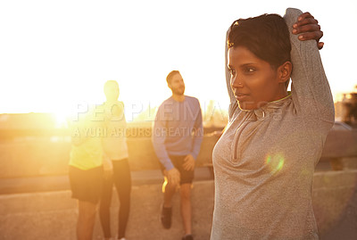 Buy stock photo Shot of a young woman stretching before a run with people in the background