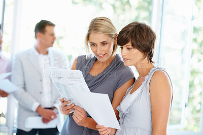 Buy stock photo Beautiful business women reading documents with colleagues in background