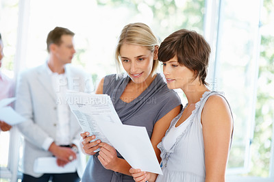 Buy stock photo Two business women reading documents with staff in background