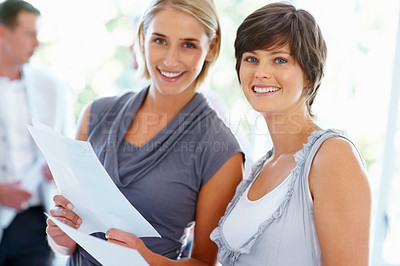 Buy stock photo Beautiful business women holding documents with team in background