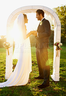 Buy stock photo Shot of the bride and groom standing outside in front of the wedding arch