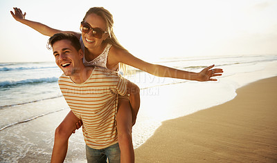 Buy stock photo A young man piggybacking his girlfriend playfully on the beach