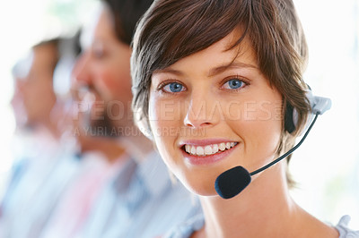 Buy stock photo Closeup of attractive female executive wearing headset with team in blur background